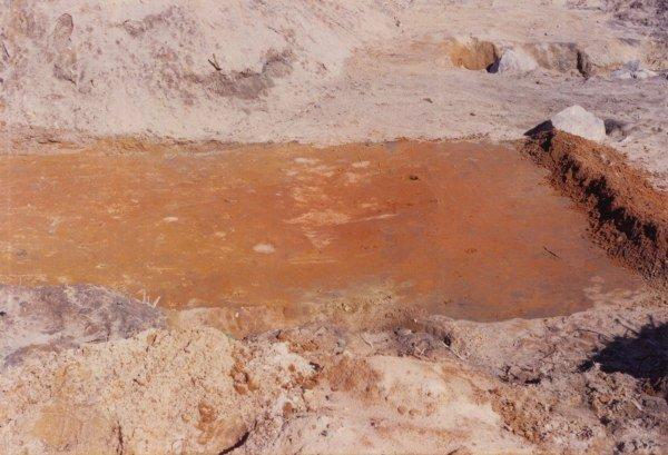 Den røde plet på gårdejer Anker Steffensens mark i Glargårdene, matr. 18a fri- lagt i eftersommeren 1990 af amatørarkæologerne Jørn og Egon Larsen, Hadsund. I forgrunden anes det først gravede hul. Billederne er scannet ind fra farvefotos og yder desværre ikke rigtig den mørkerøde farve retfærdighed.
